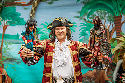 A man dressed as a pirate against a tropical backdrop holds up two puppets