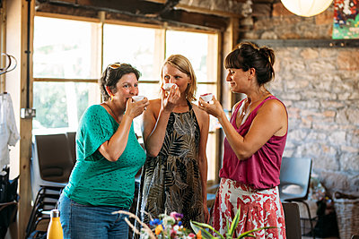Three standing guests smile and hold up natural products in tubs to smell