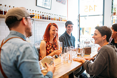 Seated guests at wooden table laugh in the distillery as they drink gin