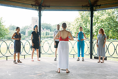 Group of six stand under Castle Park's bandstand practising vocal exercises