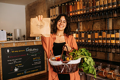 Guest proudly holds up her Refillable brown paper bag and hamper full of sustainable goods