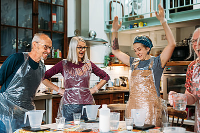 Guests in their host's kitchen laugh and lift their hands up, weighing their measuring jugs