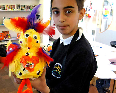 A child in a classroom holds up their colourful bird sculpture with big plumes