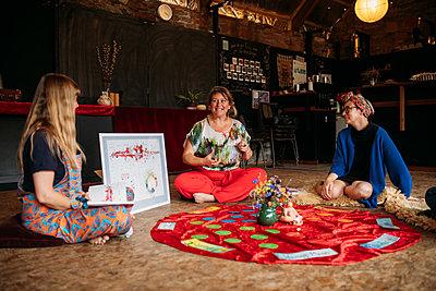 Guests and hosts sit intimately chatting around a red velvet rug and female reproductive illustration