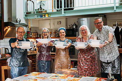 Five smiling guests stood in their host's kitchen present their mixing bowls to the camera