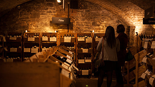 People chatting in front of wine crates in the Averys Wine Cellars