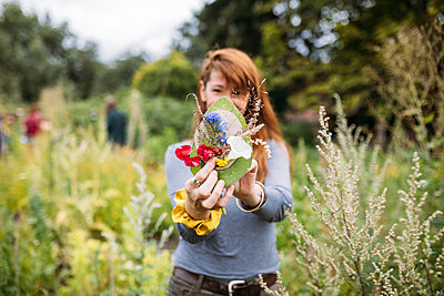 Woman holds up a mixed-media floral pendant, made of fresh flowers, dried flowers, cardboard and leaves