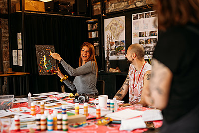 Guests holds up a intricate painting of a woodland scene in an art workshop