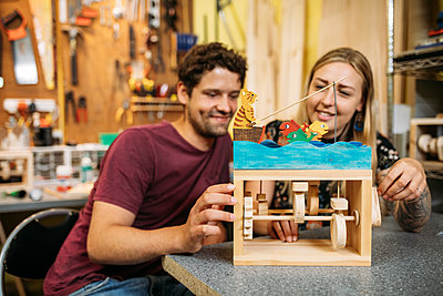 Guest admire their painted wooden mechanical toy of a cat fishing in the sea