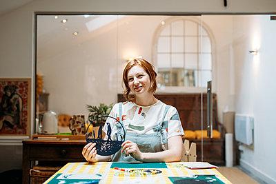 Illustrator Sarah Dennis smiles, holding up her black circle paper-cutting of penguins stood on water