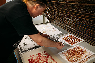 Guests lays out their abstract lithography prints in a workshop