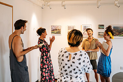 Host and guests stood in a circle have an animated discussion in a bright, airy room with artwork on the walls