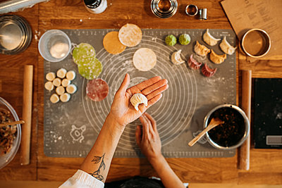 Host holds up a neat dumpling to the camera, with their other bright dumplings displayed on the chopping board beneath