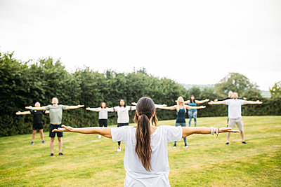 Host stretches both her arms out wide and guests mimic the posture as they practise yoga outdoors in Chew Valley's countryside