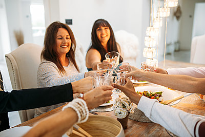 Happy guests raise their glasses and cheers, seated at a wooden table indoors with warm lighting