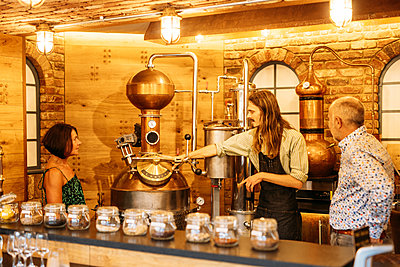 Host draws his guest's attention to a copper still pot in the distillery
