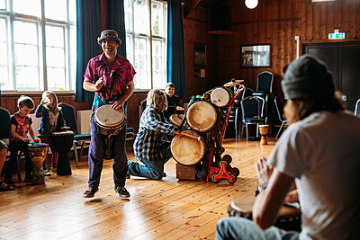 Two drummers play to a seated live audience