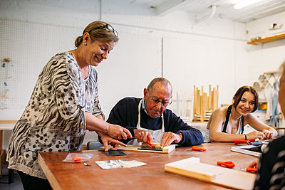 Host guides guest in workshop as they use a cutter knife