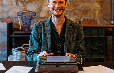 Poet Jonny Heath beams at camera, resting his hands on a typewriter