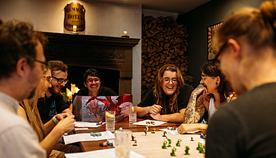 Seated guests at Bristol Gin laugh as they play D&D on the table