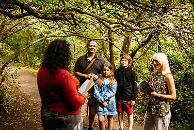 Poet Jen reads to her guests under a tree in a woodland