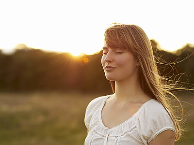 Woman closes her eyes and smiles on a sunny afternoon