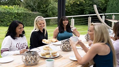 Cheerful guests chat over tea and cake, during their lunch break outdoors