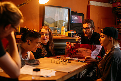 Host and guests talk amongst themselves playing Dungeons & Dragons at a wooden table