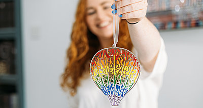 Guest holds up rainbow colourful fused glass Bristol balloon with string