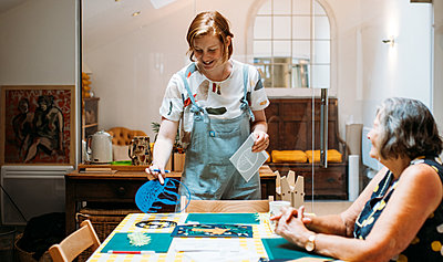 Illustrator Sarah Dennis laughs with a guest, as she places down a round blue paper-cutting of penguins on ice