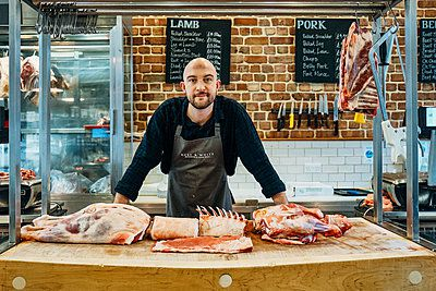 butcher stood at a counter full of meat