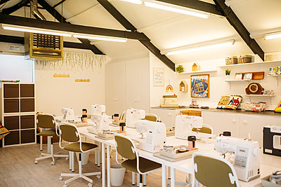 Bright sewing studio with seating, machines and counter space