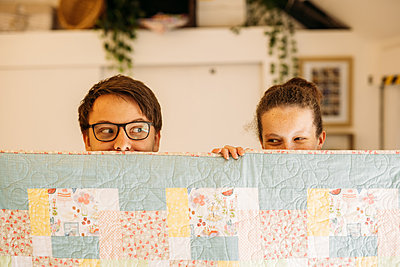Two guests hold up large patchwork quilt, peering their heads over it
