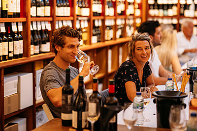 One guest lifts up glass of wine to smell at DBM in-store tasting