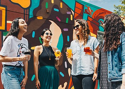 Guests holding pints laugh, standing in front of colourful mural outside