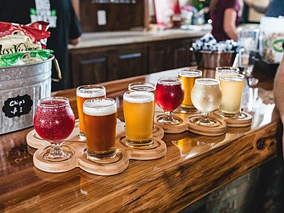 Different beer varieties on wooden coasters lined up for a tasting