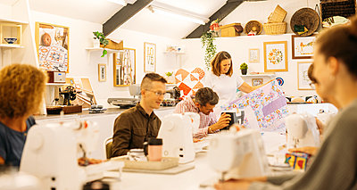 Host holding a large patchwork quilt smiles, guests concentrate on their sewing machines