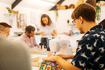 Guests sit & sew at their desks in Quilt Factory's modern airy studio