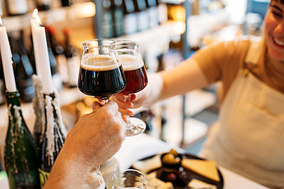Two guests toast their wine glasses filled with beer inside Two Belly's shop