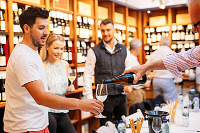 Host pours a guest sparkling wine during a tasting event inside DBM's traditional wine shop