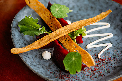 Gourmet vegan beetroot dish on ceramic blue plate