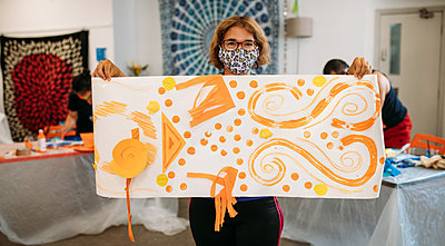 Guest presents an abstract orange mural to the camera made with mixed-media