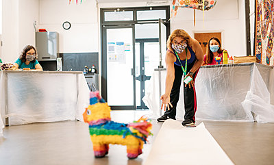 Guest bends over taking an aim at a piñata animal at A&K's Playground obstacle