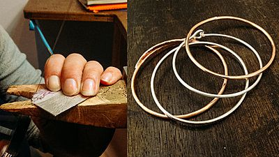 hands making silver bangles in a workshop