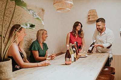 Guests and hosts discuss the bottles of wine in KASK's dining area