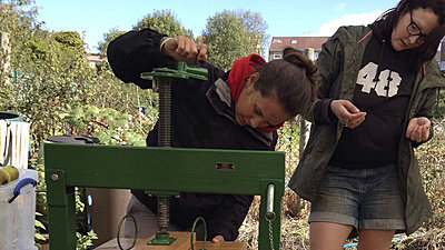 Guest uses a large apple squeezer at the Community Orchard