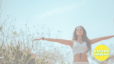 Woman stretches out both arms wide in empowering pose