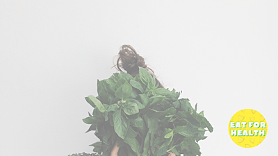 Woman holds green herbs over her face to cover it