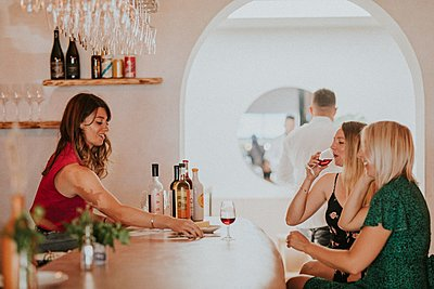Waitress presents guests with red wine and cheese at KASK's bar