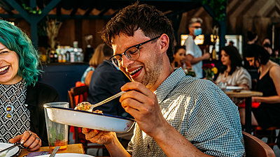 Happy guest tucks into their plate of food at MAZI Project fundraiser